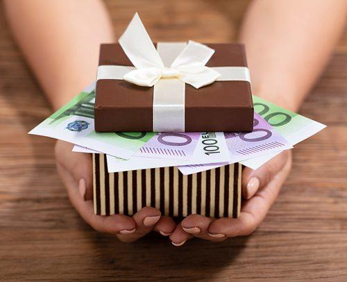 how much to spend on a wedding gift hands holding cash in gift box