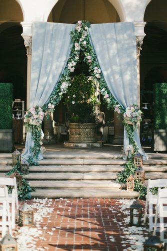 silver sage wedding ceremony arch with cloth and flower greenery onelove photography