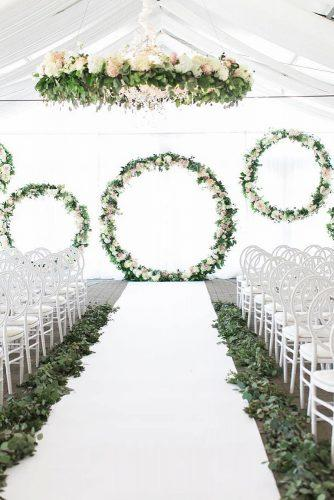 spring wedding décor under white tent woth greenery aisle round shapes arch with roses laurenkurc