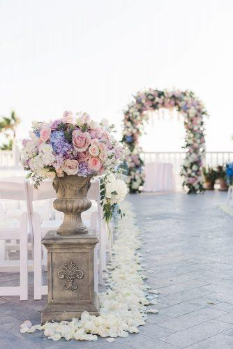 spring wedding decor aisle with gentle pink blue lilac flower petals and stone vaces valorie darling photography