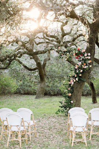 spring wedding decor garden ceremony altar with real tree backdrop with flowers and greenery julie wilhite