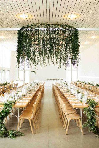 spring wedding decor indoor wedding reception with hanging greenery tablerunners nicholsphotographers
