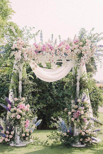 spring wedding decor outdoor ceremony altar with gentle spring blue lilac pink flowers white cascading orchids and cloth beigeweddings