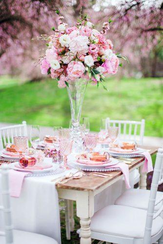 spring wedding decor tall flower centerpiece in glass vace with pink peonies caroline ross photography