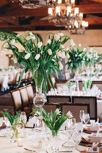 spring wedding decor tall flower centerpiece in glass vace with white tulips annaperevertaylo