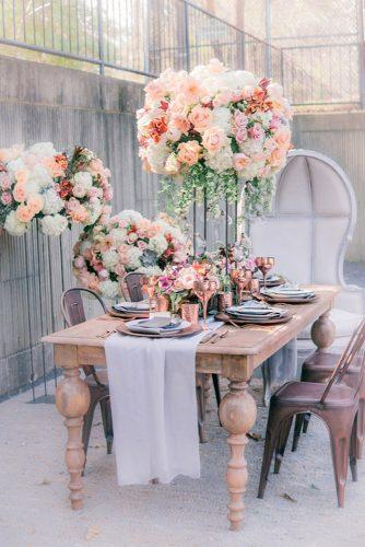 spring wedding decor tall flower centerpiece with roses and greenery on wooden table manda weaver photography