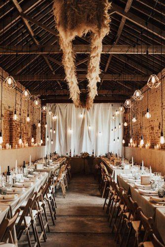 bohemian wedding decorations barn wedding reception under pampas grass and lighting darinastoda