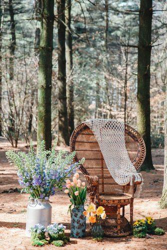 bohemian wedding decorations bohemian chair surrounded by vases with flowers maria bryzhko