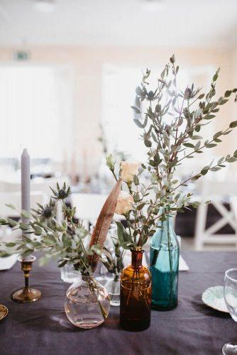 bohemian wedding decorations centerpiece with greenery branch feathers and glass vases and bottles patrick karkkolainen