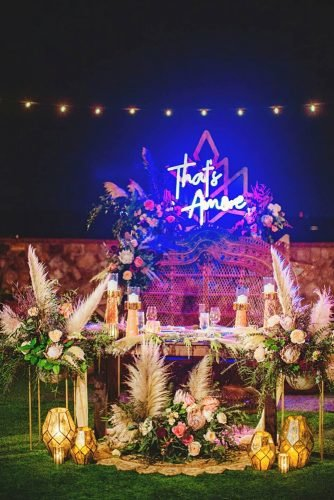 bohemian wedding decorations pampass grass neon and flowers on outdoor reception jasonmizephoto