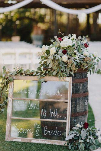 bohemian wedding decorations signs on old window frame near with wine barrel and red flowers kristen curette photography