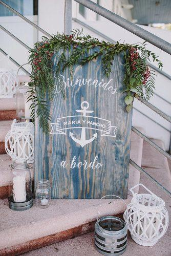 nautical wedding grey wooden sign with anchor greenery and candles raquel benito