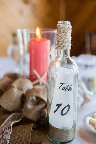 nautical wedding ideas glass bottle with stand and tablenumber coral candle elizabeth henson photos