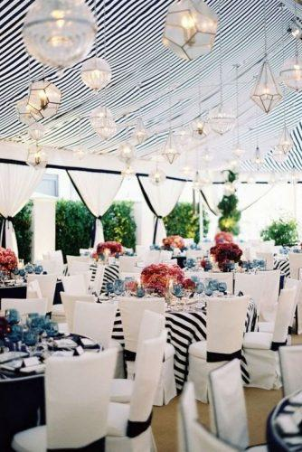 nautical wedding reception under the tent with black stripes geometry hanging lights and red flowers jose villa