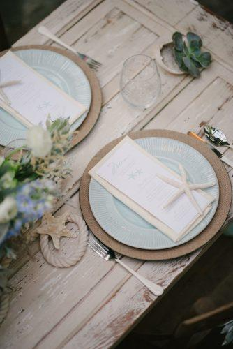 nautical wedding table seatind with sea stars ropes and blue plates lauren rae photography