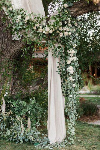 sage green wedding backdrop with white roses greenery and cloth almond leaf studios