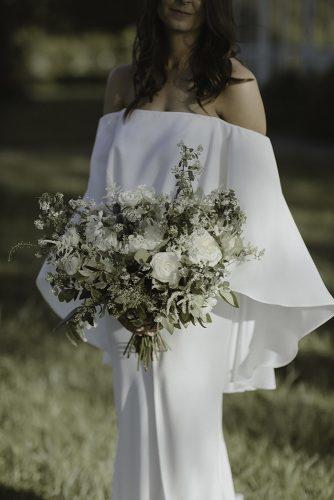 sage green wedding bouquet with white flowers and greenery in hand of the bride in original bridal dress jenny demarco weddings