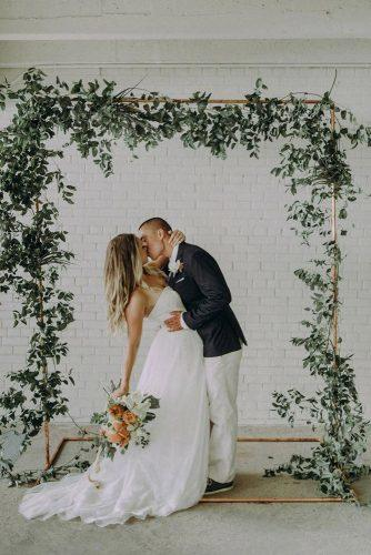 sage green wedding greenery arch groom and bride kissing at the ceremony autumn berrier