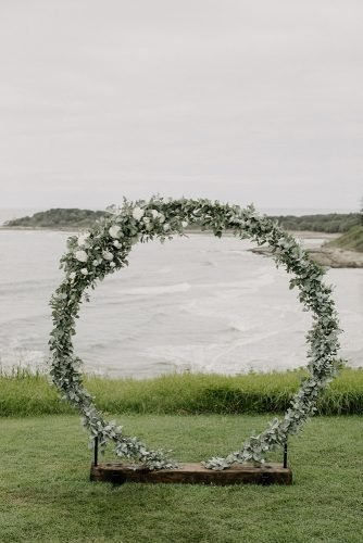 sage green wedding round shaped outdoor altar with white flowers heart and colour