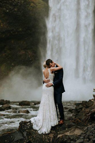 wedding photographers amazing photo of newlyweds near waterfall sararogersphotography