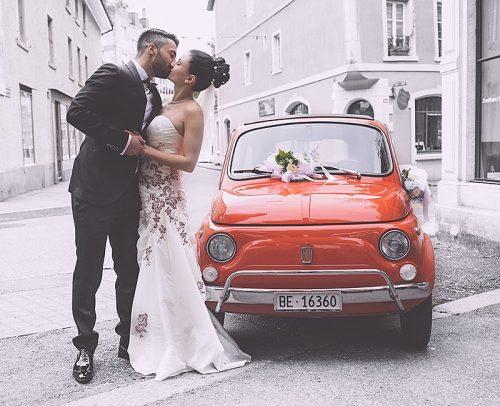 how much does a wedding photographer cost beautiful newlyweds kissing near car