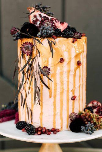rust wedding color drip cake with pomegranate fruit and berries thesantosandco