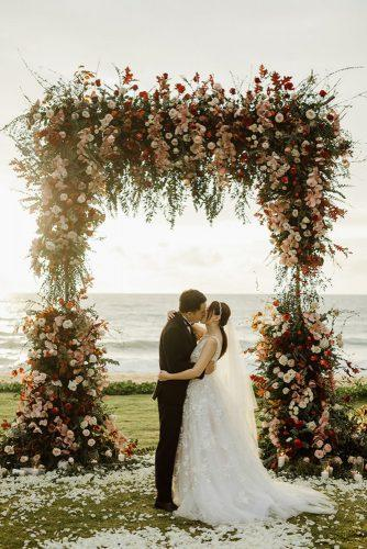 rust wedding color high bridal arch with flower red white roses on the beach alen karupovic photography