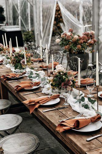 rust wedding color reception under transparent tent with white tablerunners candles and flowers alexmari_