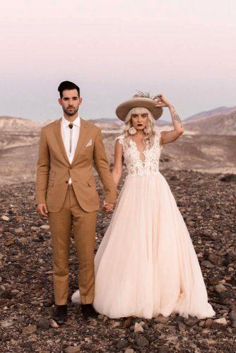 rust wedding color stylish bridal couple in desert blonde bride in hat groom in bolo tie dillon_ivory