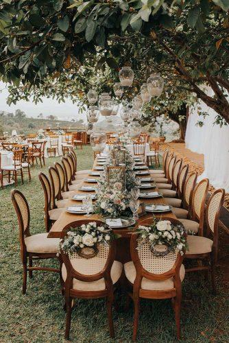 summer wedding trends outdoor reception table with hanging candles and flower tablerunner studio croma