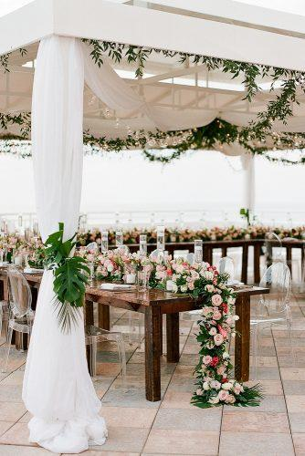 summer wedding trends reception under white tent with flower table runner and hanging greenery the ganeys
