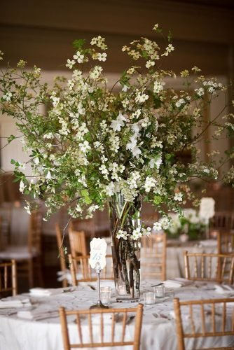 tall wedding centerpieces glam rustic greenery and white flowers in glass vase chris bailey photography