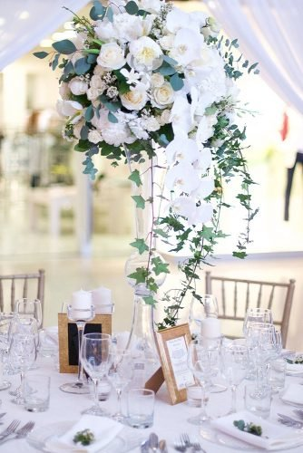 tall wedding centerpieces tall glass vase with white orchid flowers and greenery issa mariage