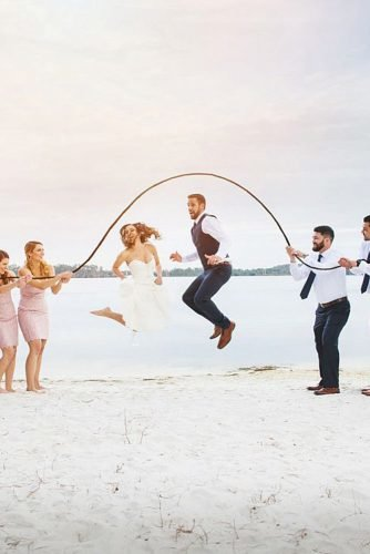 wedding party pictures groom and bride jumping rope at the beach lotus eyes photography