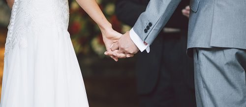 simple wedding ceremony script newlyweds holding hands featured