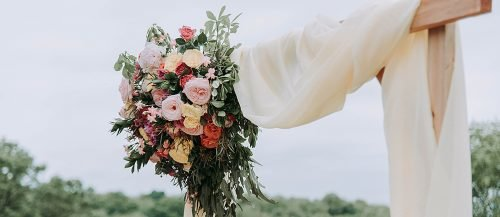 wedding arch fabric decor with flowers featured