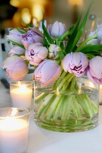 wedding centerpieces lilac tulips in glass vase with candles gerilyngiannaevents