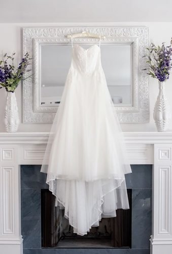 hanging wedding dress dress on white mirror hollydphotography