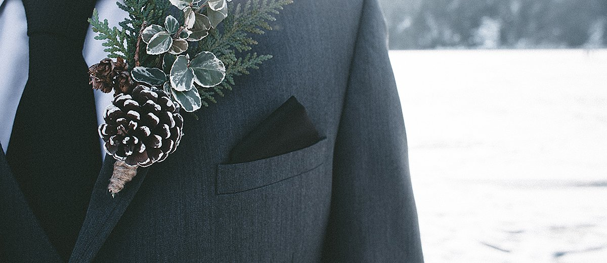 christmas wedding ideas groom in suit with boutonniere with cone featured