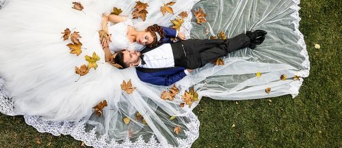 fall wedding party bride and groom together in the leaves featured