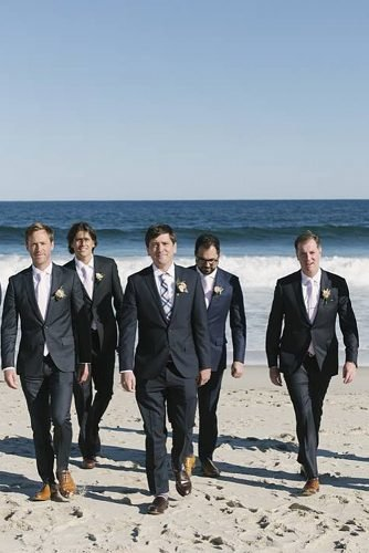 groomsmen photos groom and groomsmen walking on beach