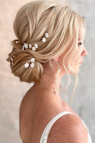 wedding updos textured low bun on blonde hair with small white flowers kasia_fortuna