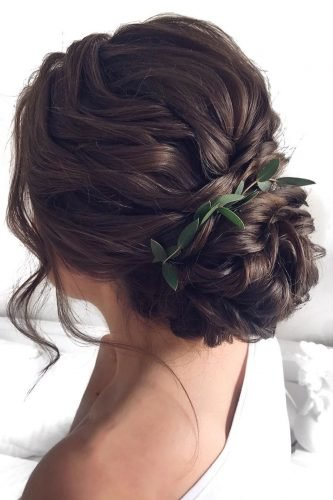 wedding updos wavy vloume low bun with greenery mpobedinskaya