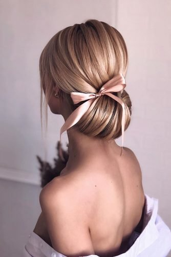bridesmaid hairstyles low smooth chignon with pink bow shiyan_marina