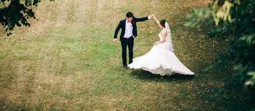 modern country love songs bride and groom dancing at field featured