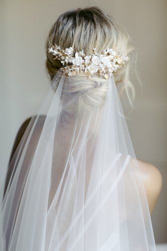 wedding hairstyles with veil low bun with white flower pin taniamarasbridal