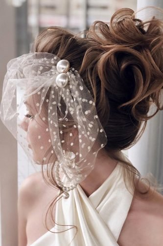 wedding hairstyles with veil textured high bun with vintage accessory antonina_romanova
