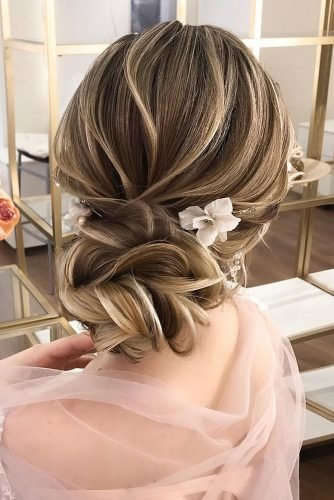 wedding updos for medium hair volume textured low with flower pin alyona_beauty_muah