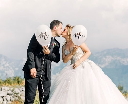 wedding announcement wording man and woman kissing while holding balloons