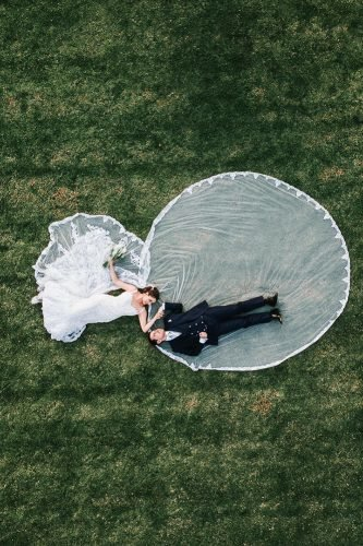wedding photography trends drone photogrphy bride and groom lie on the grass progat